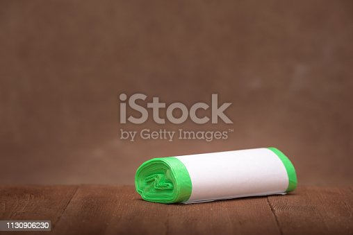 istock Roll green eco garbage bag with copy space isolated on brown wood background. 1130906230