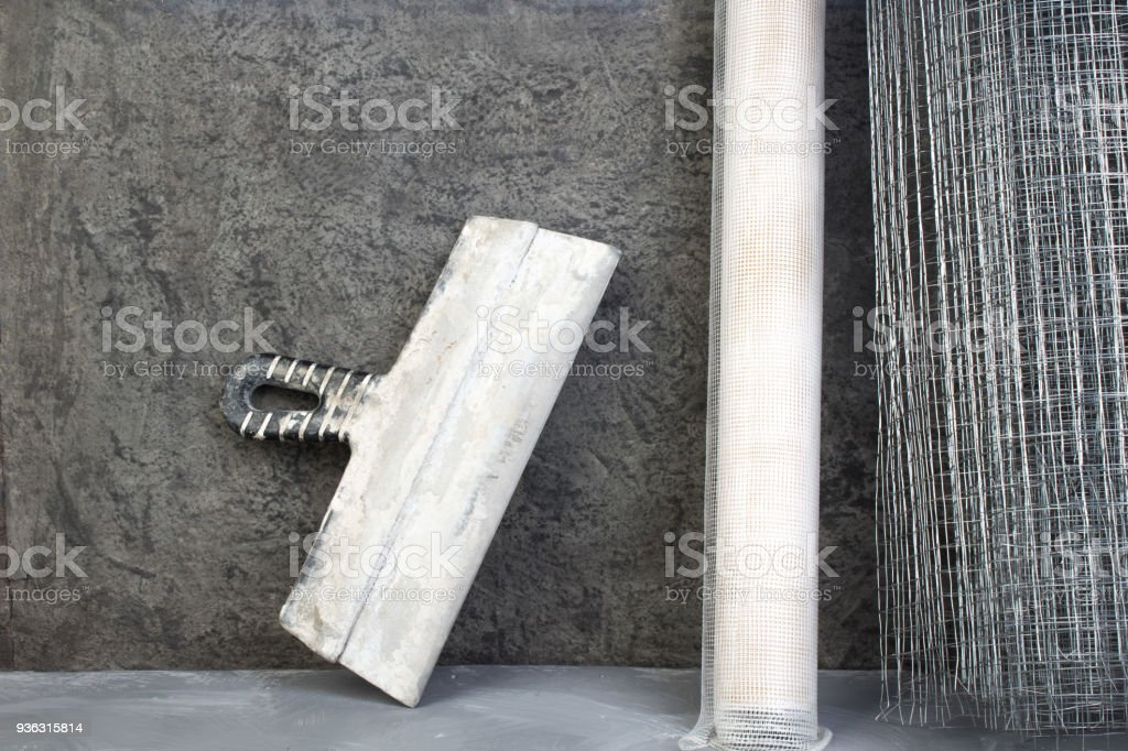 roll mesh for plastering, putty knife on the gray concrete background. Copy space. Top view stock photo