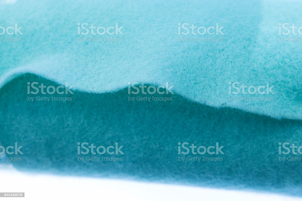 A roll of composite soft fiber. Focus on edge of fabric stock photo
