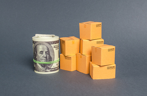 1155852718 istock photo Roll of dollars and cardboard boxes. Business and industry. The concept of commerce and trade. retail and distribution. Performance efficient production. Production and export of products and goods. 1179020276