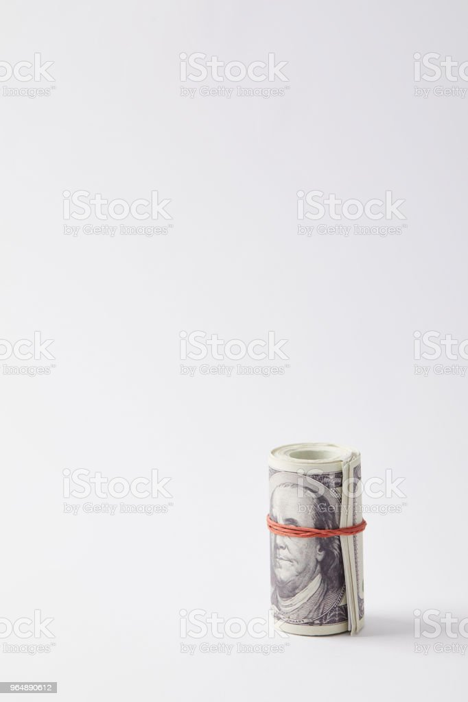 roll of dollars tied with red rubber band on white royalty-free stock photo