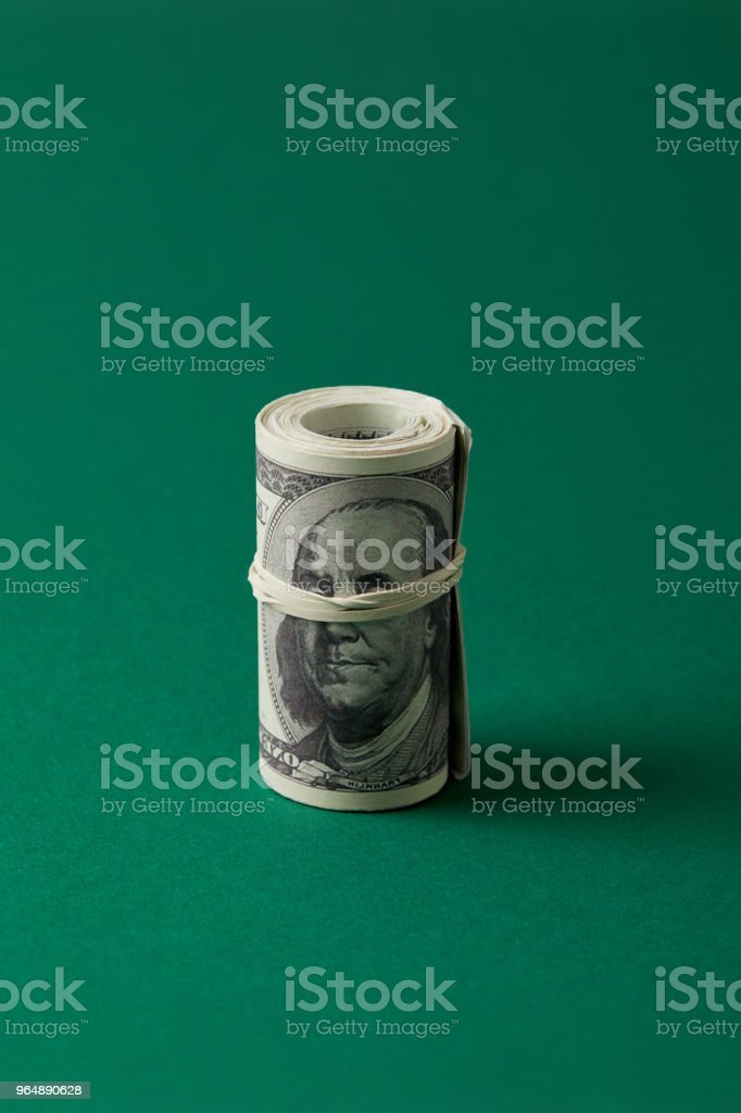 roll of dollars tied with rubber band on blue surface royalty-free stock photo