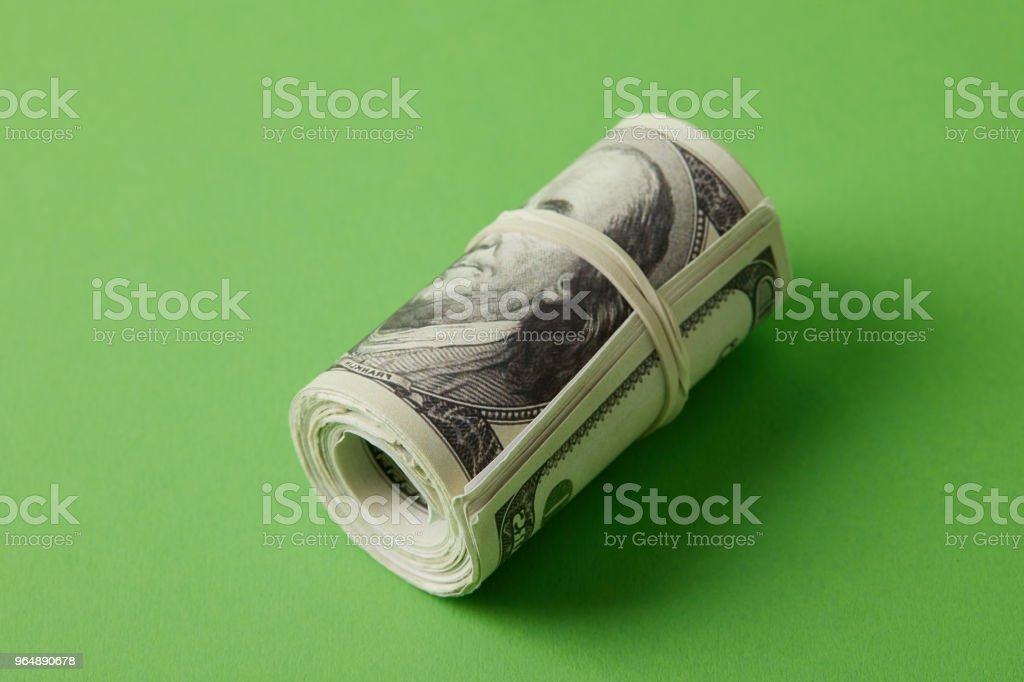roll of dollars tied with rubber band on green surface royalty-free stock photo