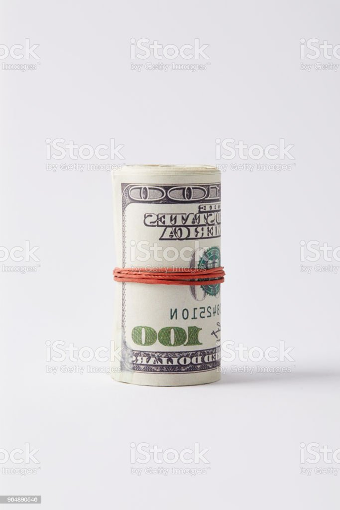 roll of dollars tied with rubber band on white surface royalty-free stock photo