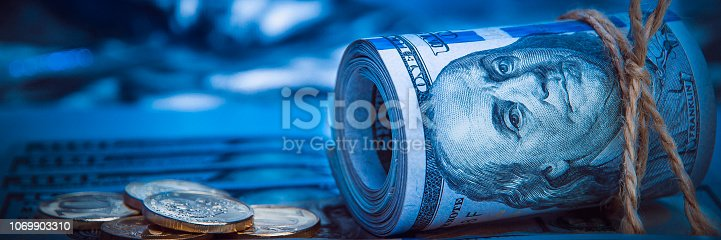 istock A roll of dollars with coins on the background of scattered one hundred dollar bills in blue light. 1069903310