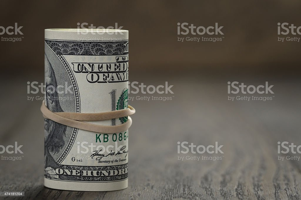 roll of new style hundred dollar bills stand on table stock photo
