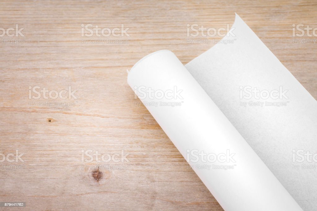 Roll of paper on wood table background. Engineer blueprint for draft work. Blank document for your design. stock photo
