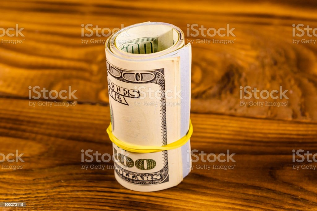Roll of the one hundred dollar bills with rubber on wooden table royalty-free stock photo