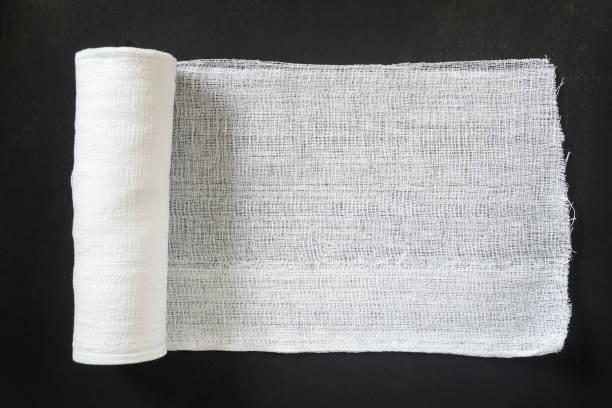 A roll of white medical bandage on a black background. A roll of white medical bandage on a black background. bandage stock pictures, royalty-free photos & images