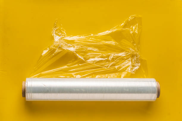 roll of wrapping stretch film for packing at colorful background isolated stock photo