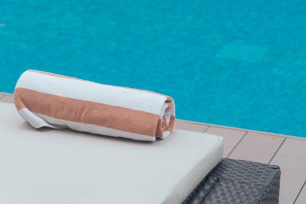 Rollen Sie weiches Handtuch auf einem Sonnenbett in der Nähe eines Pools. – Foto