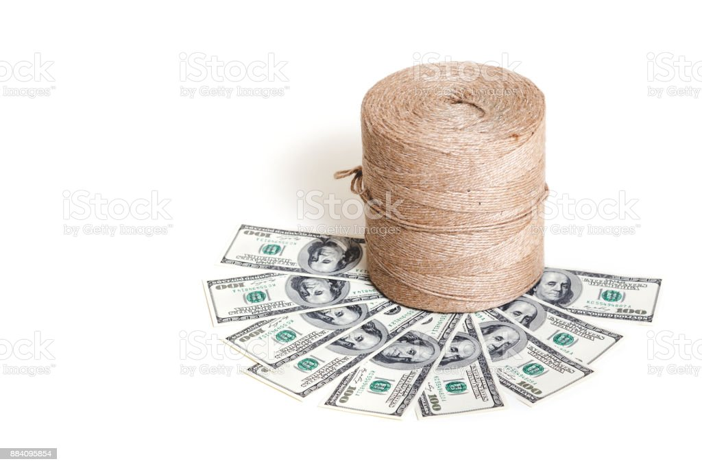 Roll twine stands on dollar banknotes stock photo