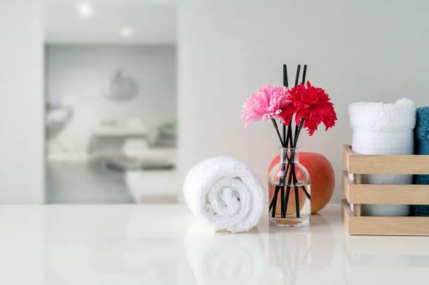Rollo de toallas blancas en la mesa blanca con el espacio de copia en el fondo de la sala de estar borrosa. - foto de stock