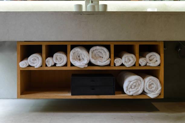 Rolle weiße weiche Handtücher in eingebautem Holzregal – Foto