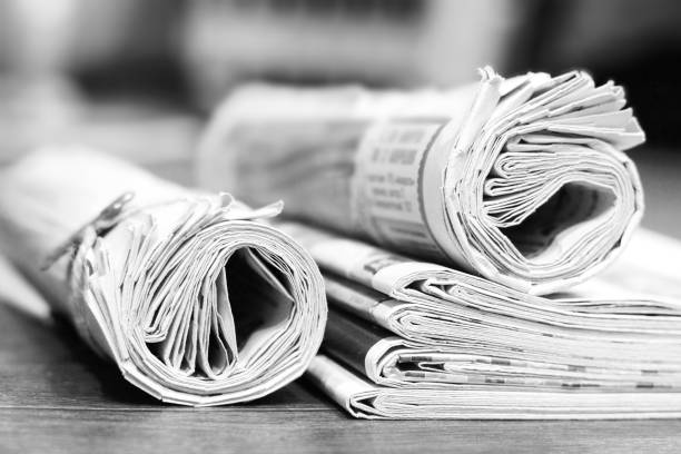 rolled and folded newspapers on wooden table - graphic print stock photos and pictures