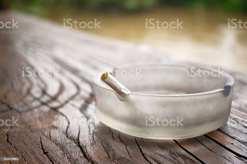 Rolled cigarette with marijuana in the ashtray stock photo