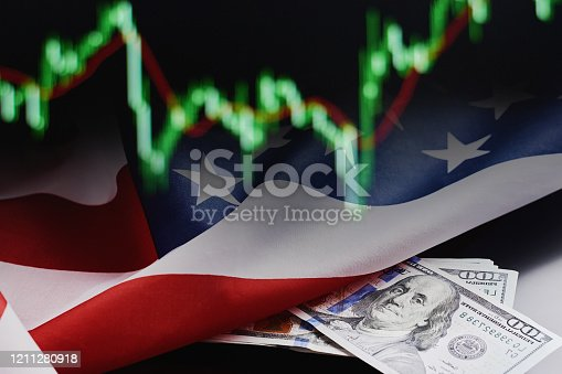 istock Rolled dollars banknotes against stock quotes background. Finance and a business concept 1211280918