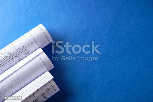 Rolled engineering drawings at blue background with copy space.