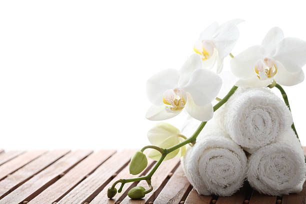 Rolled face cloths on a spa bench stock photo