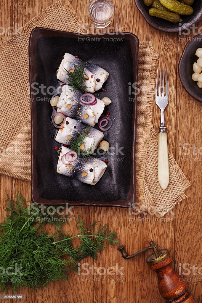 Rolled herring in vinegar, served with onions and pickles. stock photo