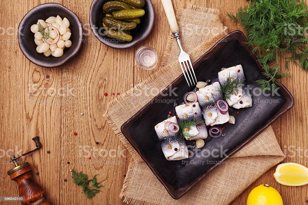 Gerollter herring in Essig, serviert mit Zwiebeln und sauren Gurken. Lizenzfreies stock-foto