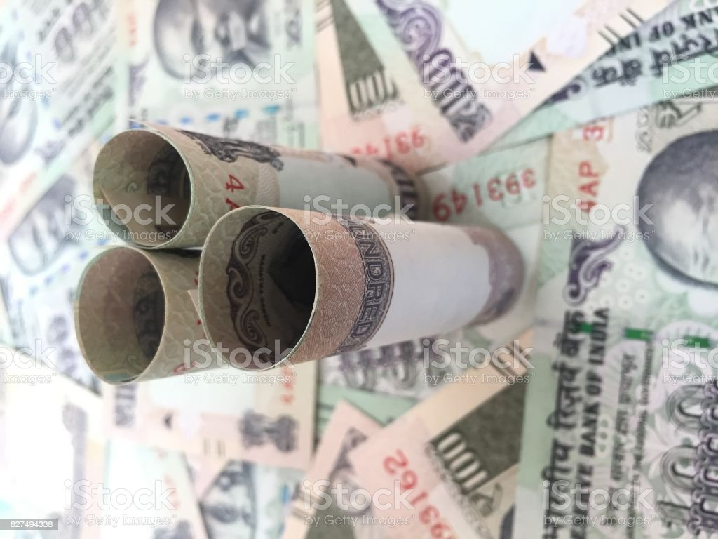 Rolled Indian Hundred Rupees Notes With 100 Rupee Background