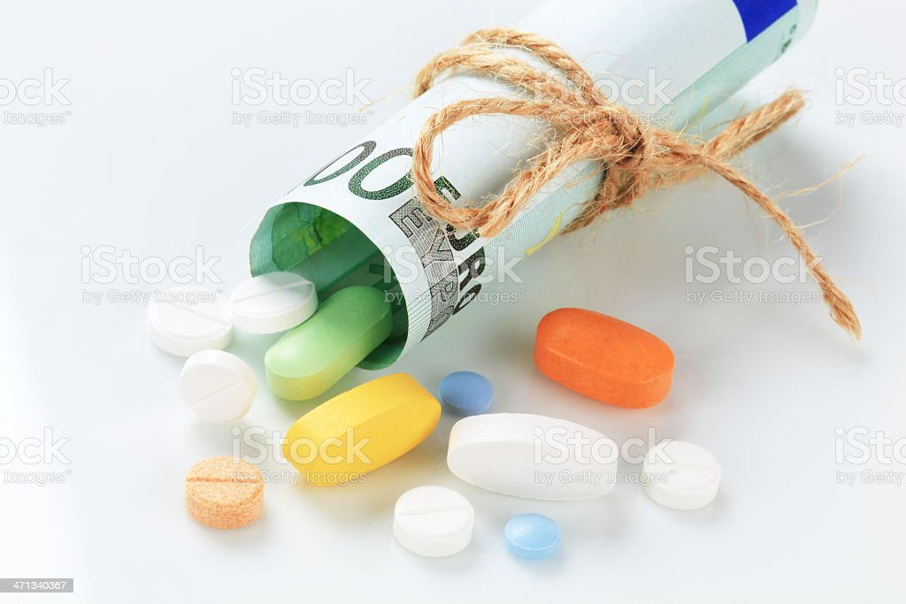 Rolled money and pills royalty-free stock photo