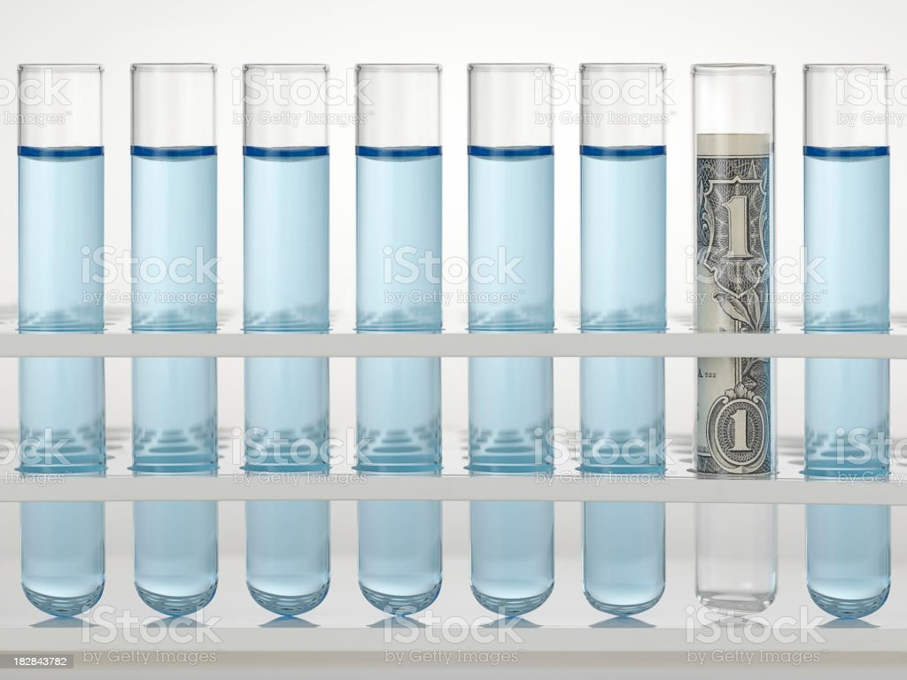 rolled money in test tube stock photo