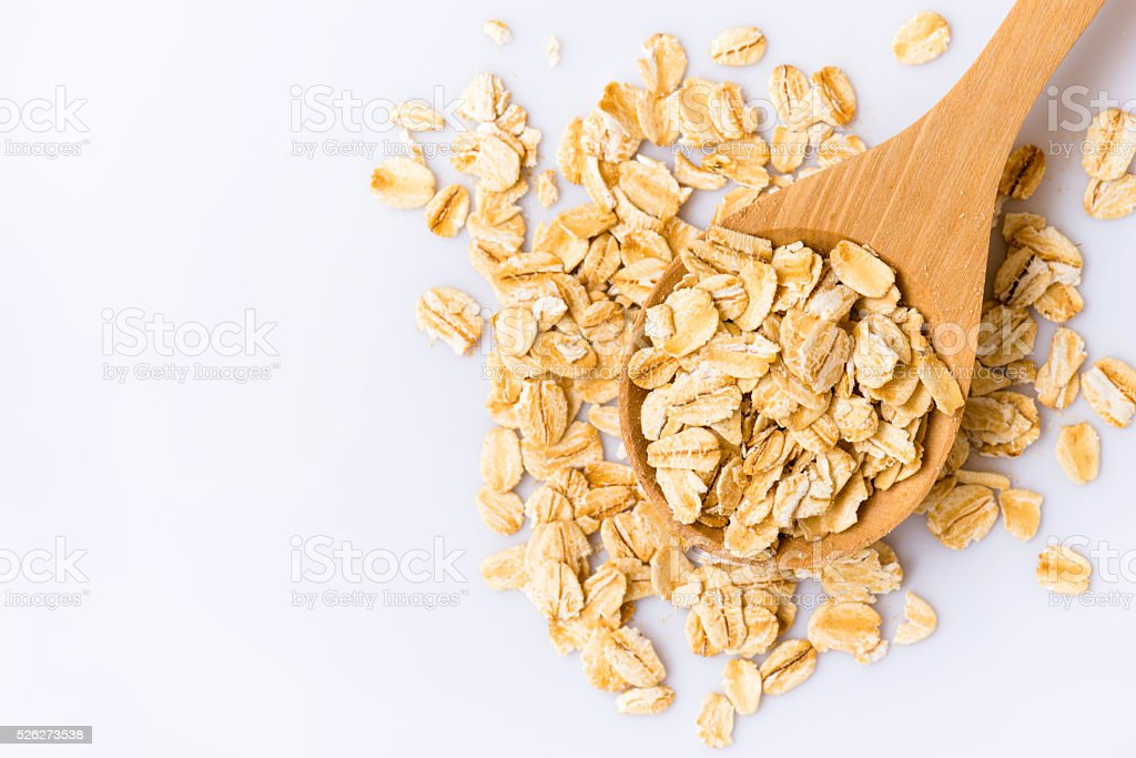 Rolled oats in a wooden spoon on white background stock photo