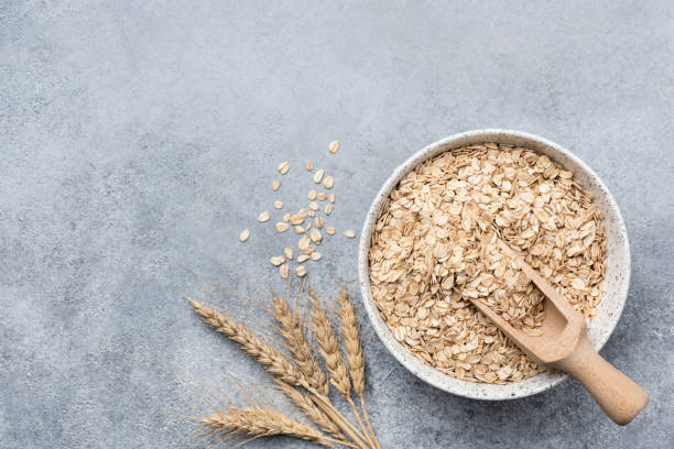 Rolled oats, oat flakes in bowl on concrete background Rolled oats, oat flakes in bowl on concrete background. Top view with copy space. Healthy food, healthy eating, dieting, weight loss and health care concept oat crop stock pictures, royalty-free photos & images