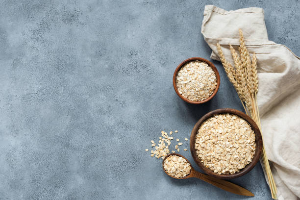 Rolled oats, oat flakes, whole grain oats Rolled oats, oat flakes, whole grain oats in wooden bowl, linen textile and golden ears of wheat on concrete background with copy space for text ear of wheat stock pictures, royalty-free photos & images