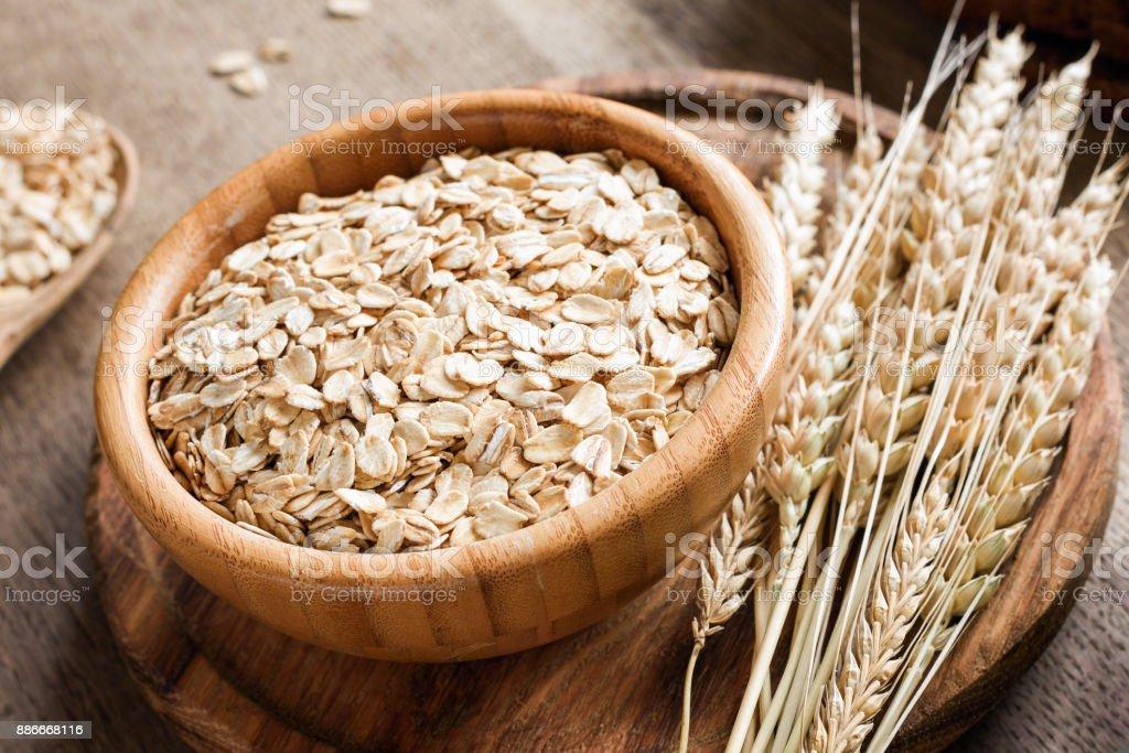 Flocons d'avoine ou de flocons d'avoine et épis de blé d'or sur fond en bois. - Photo