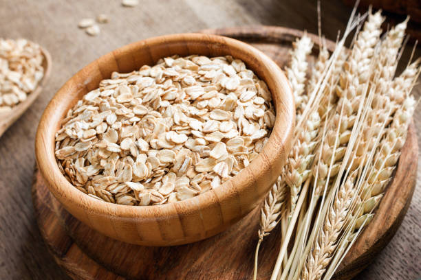 Rolled oats or oat flakes and golden wheat ears on wooden background. Rolled oats or oat flakes and golden wheat ears on wooden background. Concept of agriculture, healthy eating, healthy lifestyle oatmeal stock pictures, royalty-free photos & images