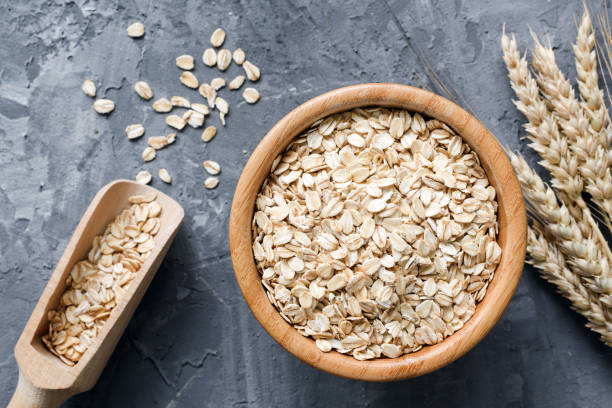 rolled oats or oat flakes in wooden bowl on stone background. - porridge foto e immagini stock