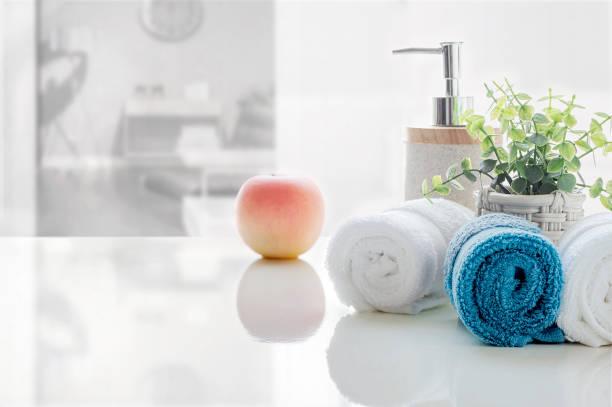 Laminado de toallas limpias en la mesa blanca con fondo borroso de la sala de estar, copiar el espacio para la exhibición del producto. - foto de stock