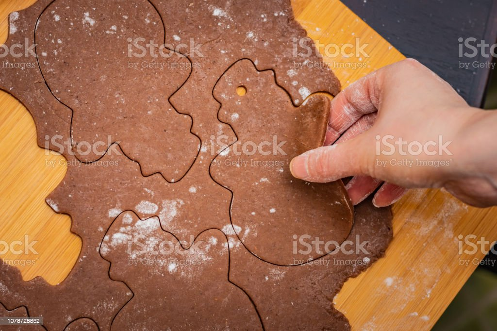 Rolled out dough on a table top with cut-out snowmen, preparation for Christmas, baking gingerbread cookies, hand raising one snowman – zdjęcie