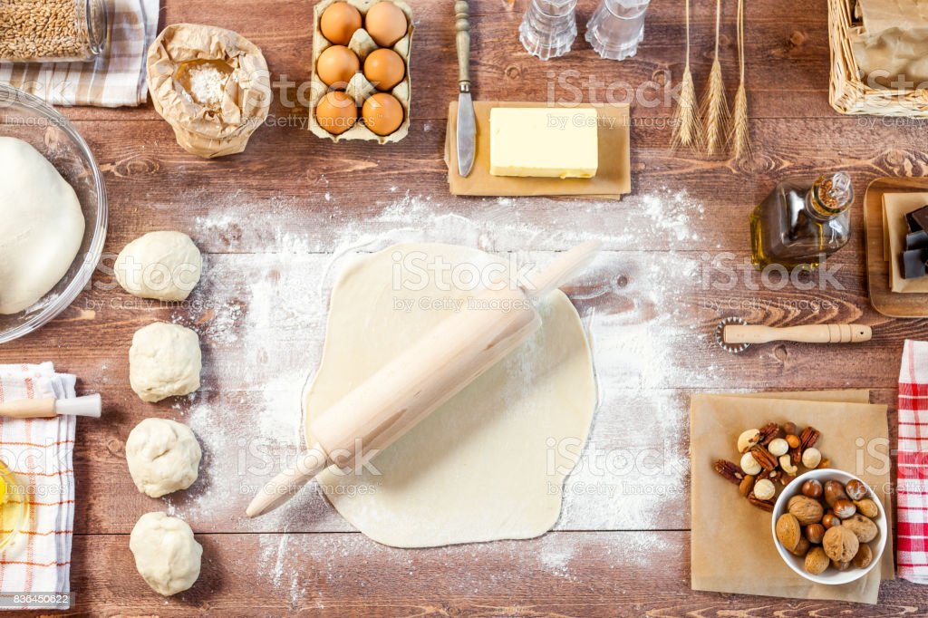 Rolled out dough on wooden table with rolling pin. Top view stock photo
