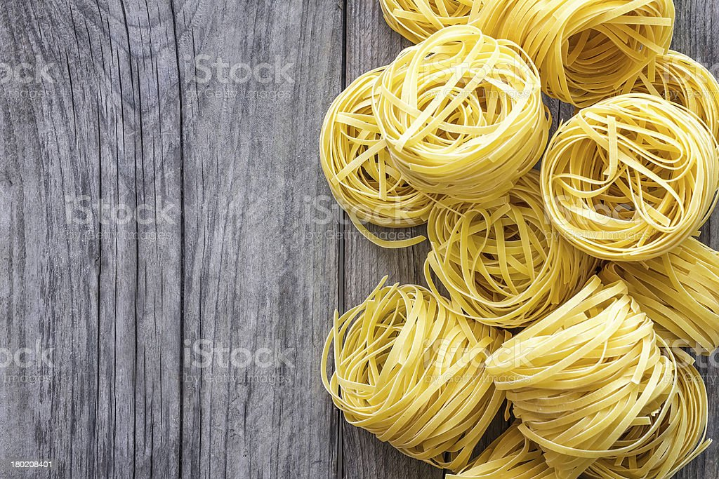 Rolled pasta that has not been cooked on a wooden table royalty-free stock photo