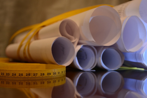 istock rolled project papers with tape measure around 12 489780512