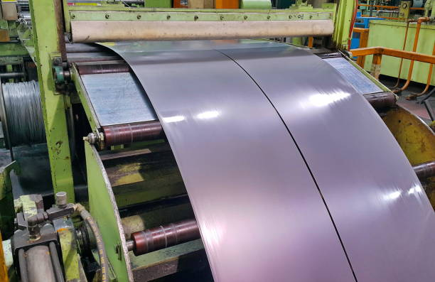 Rolled steel coil slitting process, slitter in factory warehouse, coil center stock photo