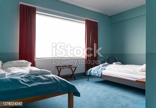 Rolled towels on white twin double beds. Furniture in bright hostel bedroom. Interior of college dorm.