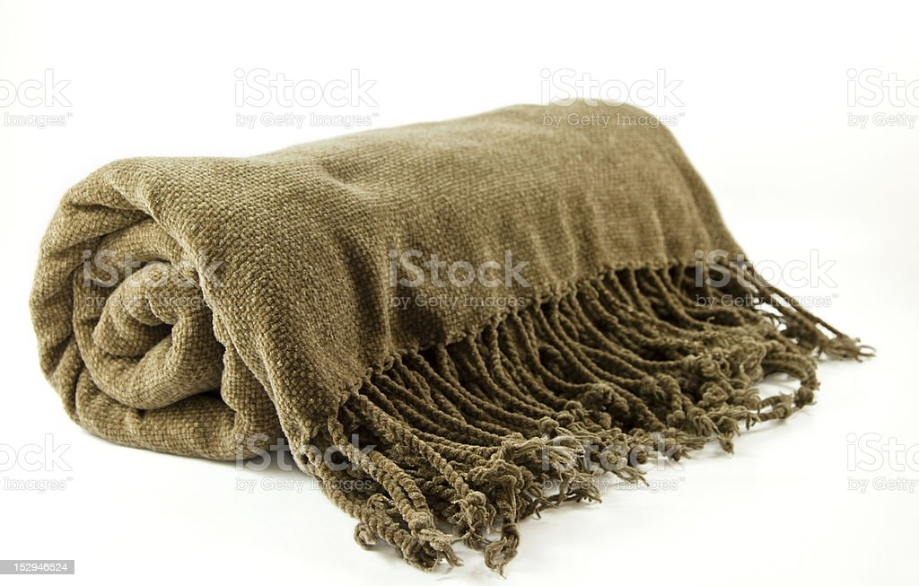 A rolled up brown blanket with cozy fringe detailing stock photo