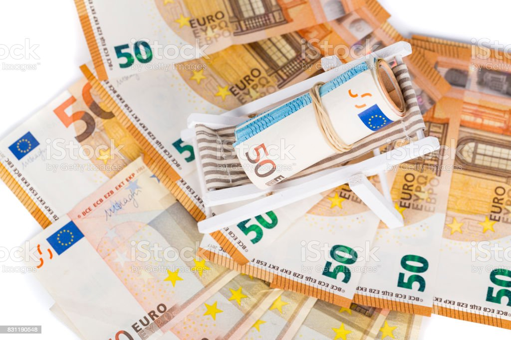 Rolled Up Bundle Of euro Banknotes On Miniature Deck Chair. stock photo