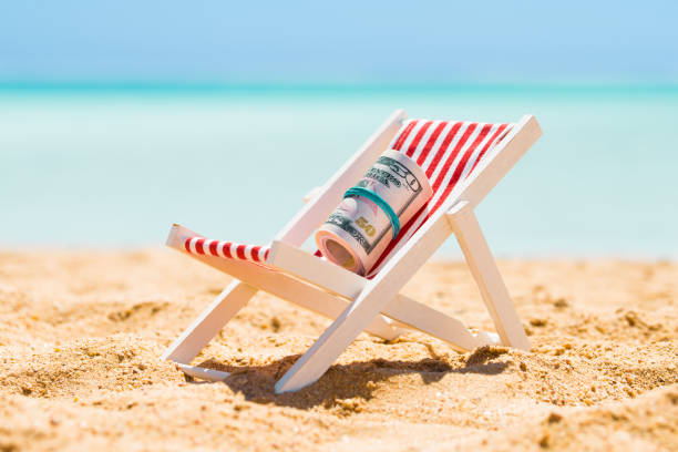 Rolled Up Bundle Of Fifty Dollar Banknotes On Deck Chair Rolled Up Bundle Of Fifty Dollar Banknotes On Miniature Deck Chair At Beach 40 kilometre stock pictures, royalty-free photos & images