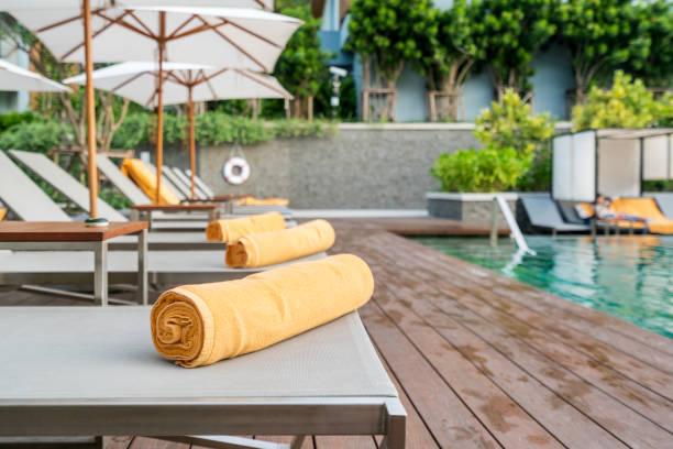 Auf eine Sonnenliege Hintergrund des Pools im Resort oder Hotel orange Handtuch aufgerollt. – Foto