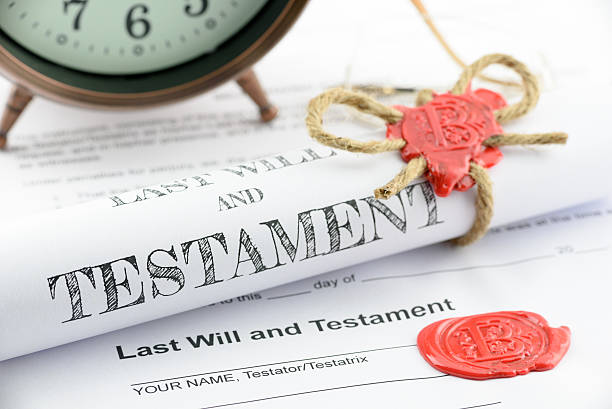 Rolled up scroll of last will and testament. Rolled up scroll of last will and testament fastened with natural brown jute twine hemp rope, sealed with sealing wax and stamped with alphabet letter B. Decorated with an antique clock on a table. last stock pictures, royalty-free photos & images