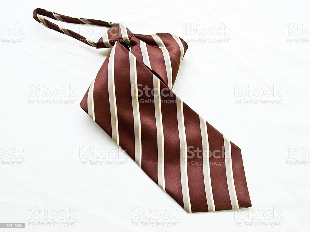 Rolled up striped brown and white tie isolated on white stock photo