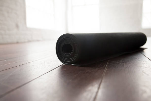 Rolled up yoga mat on natural wooden floor stock photo
