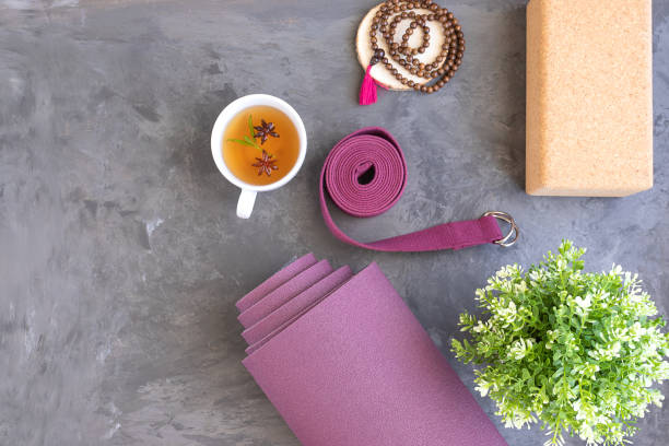 Rolled yoga mat with mala beads and Ayurveda tea for relax yoga practice y meditation. Rolled yoga mat with mala beads and Ayurveda tea for relax yoga practice y meditation. yogi stock pictures, royalty-free photos & images