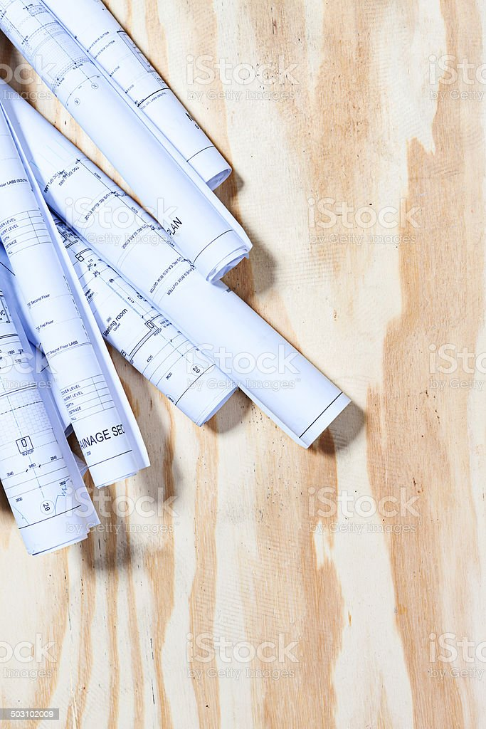 Rolled-up architectural plans on upper left of wooden background royalty-free stock photo